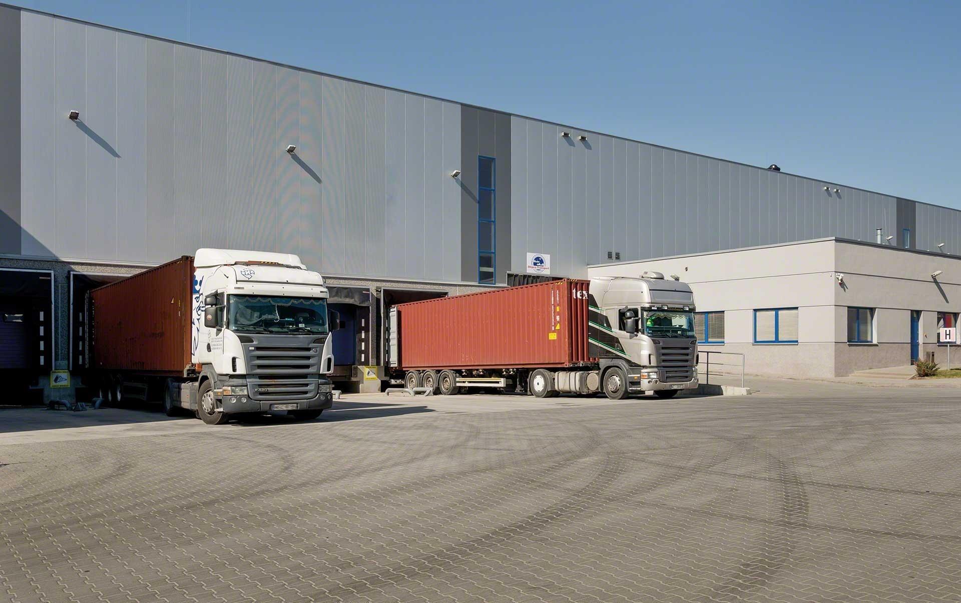 Camions qui déchargent leurs marchandises sur les quais de l'entrepôt