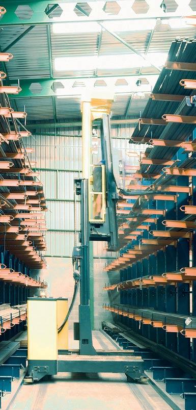 Chariot rétractable à chargement latéral dans un entrepôt de profilés métalliques.